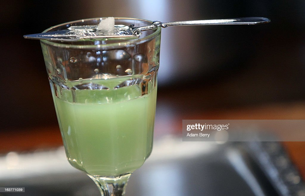 Sugar dissolves atop an absinthe spoon into a glass of absinthe at the Absinth Depot shop on March 15 2013 in Berlin Germany The highly alcoholic...
