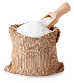 sugar with scoop in burlap sack isolated on white background. Full bag of sugar crystals closeup