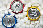 Unhealthy food concept - sugar in carbonated drinks. Sugar cubes as background and canned drinks