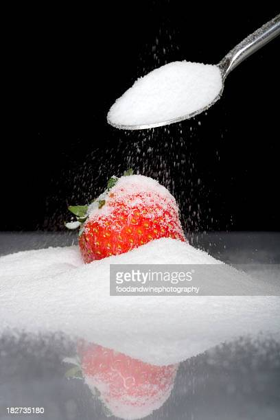 sugar on spoon black isolation with strawberry