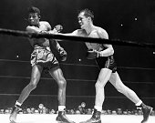 Sugar Ray Robinson takes a hard right from opponent Fritzie Zivic but it would not be enough for Sugar Ray Robinson would go on to win the bout by...