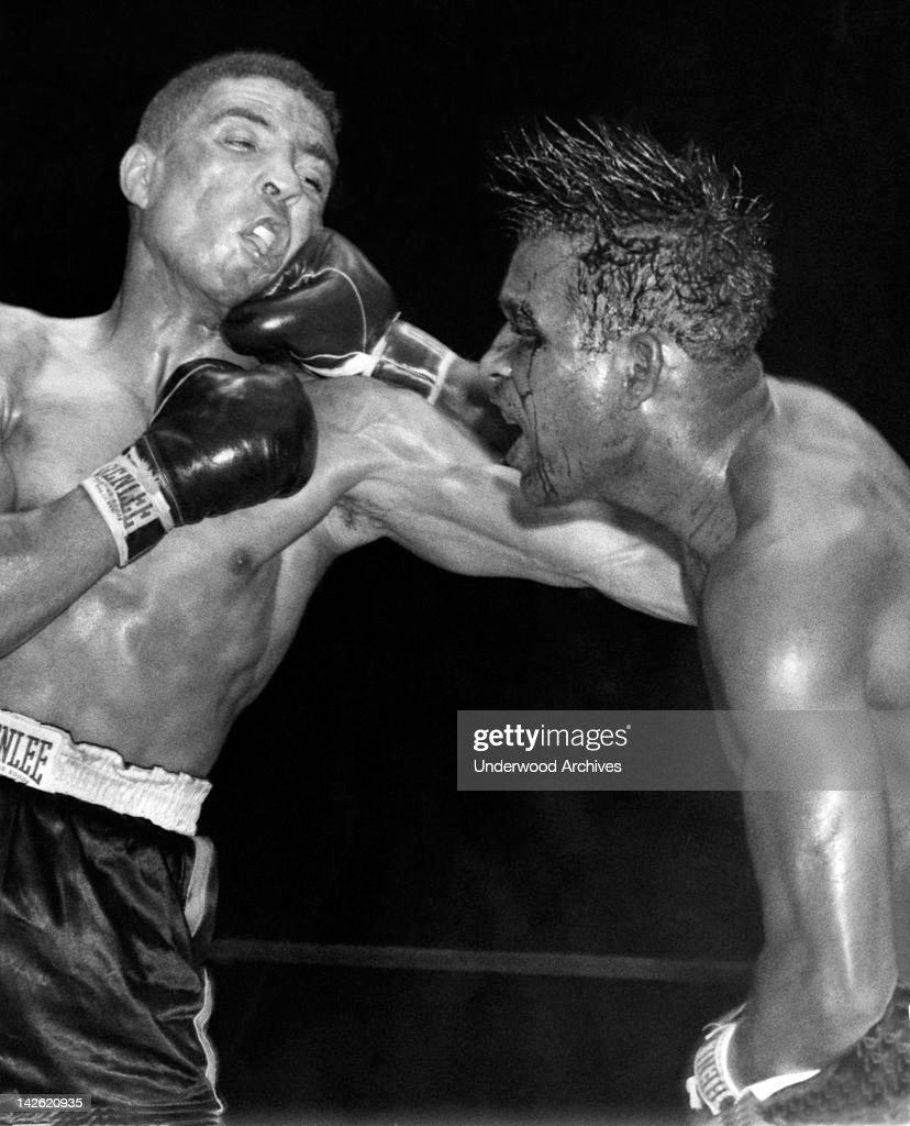 Sugar Ray Robinson throws a hard right to the jaw of middleweight champion Randy Turpin in the tenth round of their title bout at the Polo Grounds...