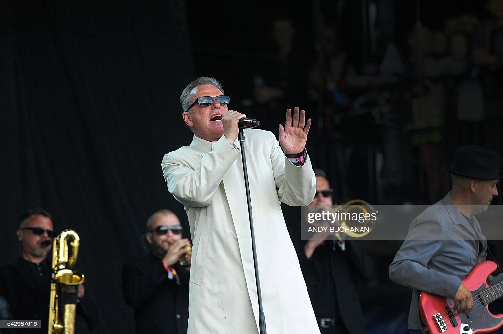 Suggs of the band Madness performs on the Pyramid Stage on day four of the Glastonbury Festival of Music and Performing Arts on Worthy Farm near the village of Pilton in Somerset, South West England on June 25, 2016. / AFP / Andy Buchanan