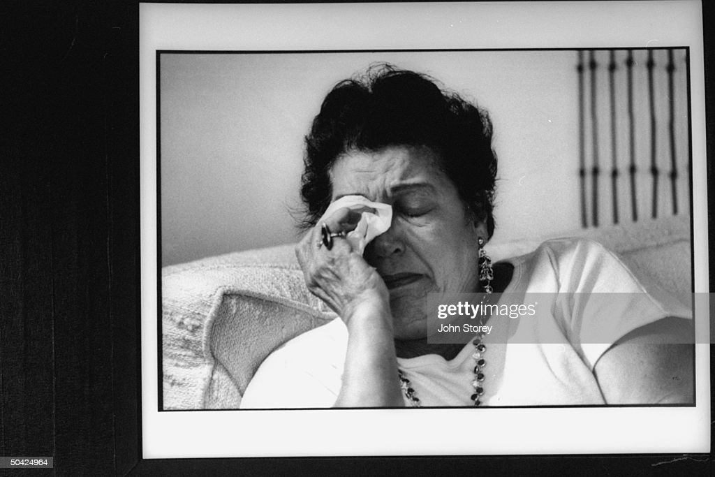 Suicide victim Collier Vale's grief-stricken mother Theresa wiping tears from her eyes w. a tissue as she recounts the details of her 39 yr. old county prosecutor son who shot himself to death because of job pressures, at home.
