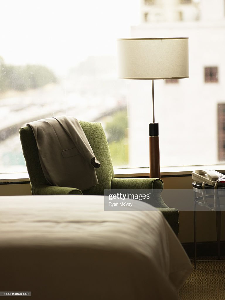 Suit jacket on armchair in hotel room : Stock Photo