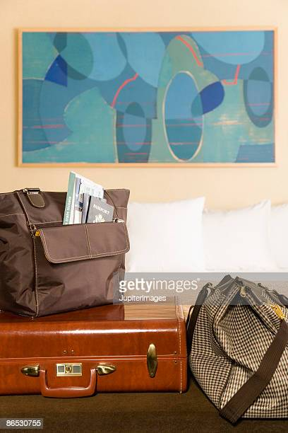 Suitcase and bags on bed