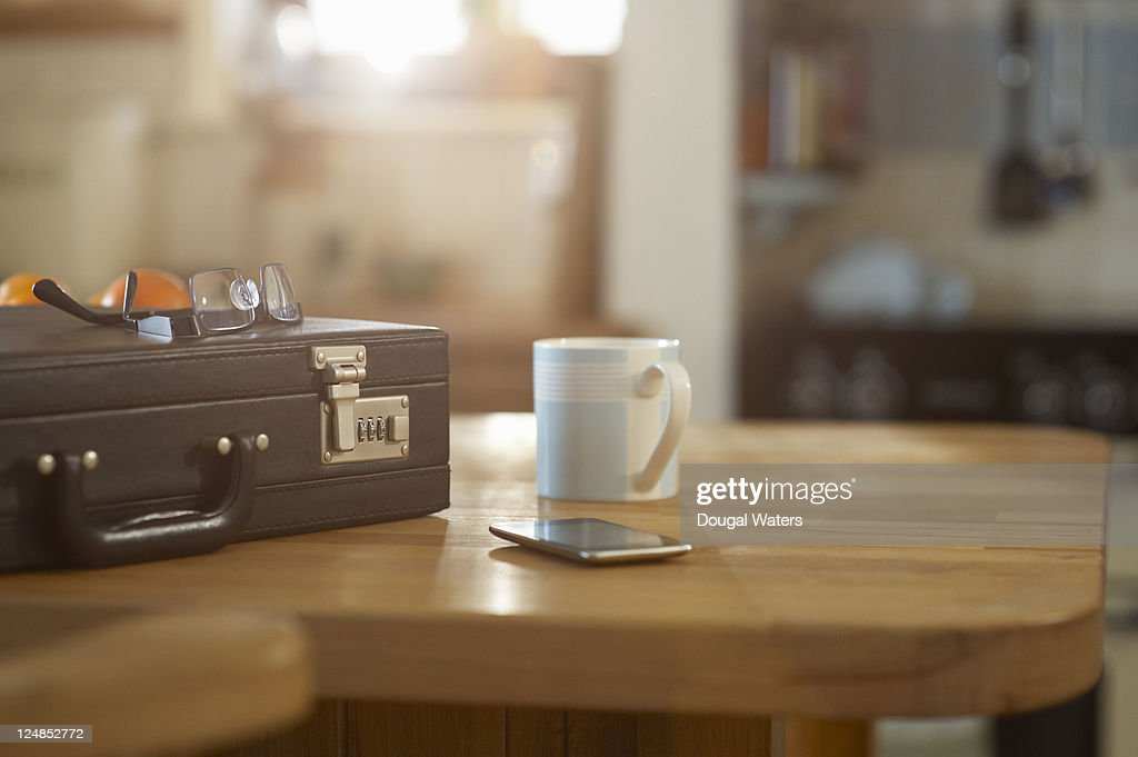 Suitcase and mobile phone on kitchen table. : Stock Photo