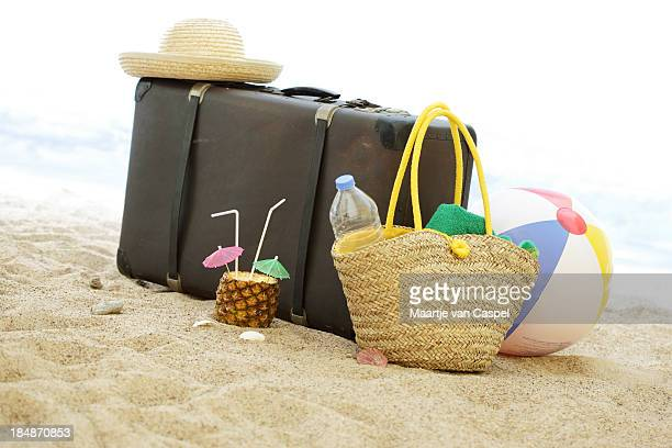 Suitcase and on the beach with summer accessories