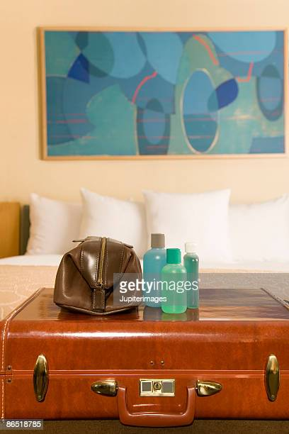 Suitcase and toiletries in hotel room