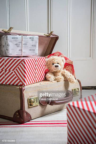 Suitcase filled with wrapped gifts and teddy bear