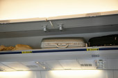 Suitcase in overhead locker on airplane