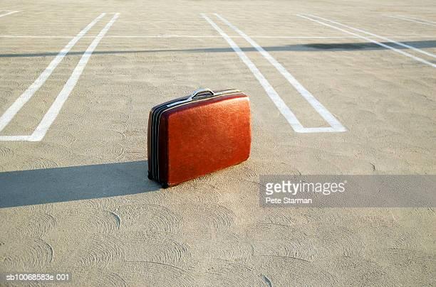 Suitcase on empty parking lot