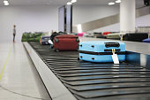 Suitcase or luggage on conveyor belt in the airport waiting