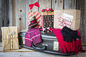 horizontal Christmas image of scarf and mitts along with gifts lying on a black suitcase all ready and packed to go on a Christmas vacation.