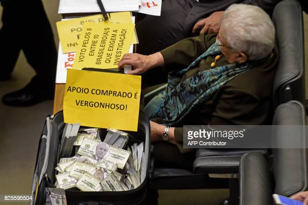 A suitcase with fake US dollar bills bearing the face of Brazilian President Michel Temer and a sign reading 'purchased support is shameful' as a...