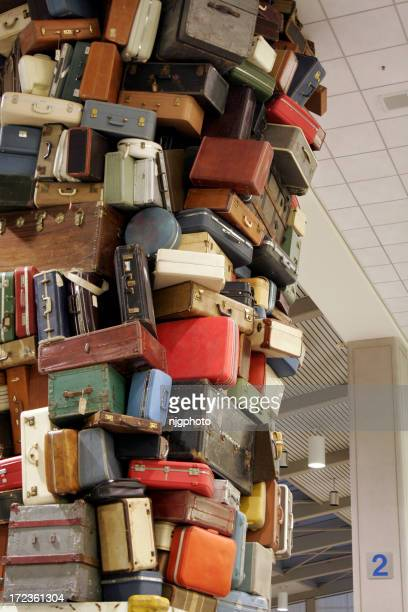 Suitcases stacked dangerously and disorderly in a room