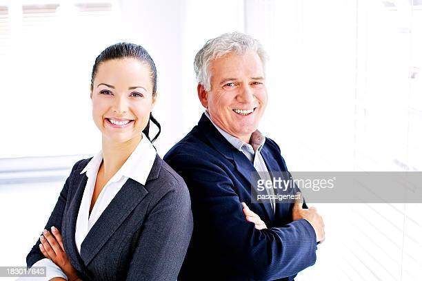 Suited man and woman standing shoulder to shoulder