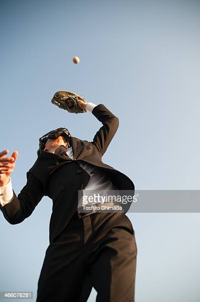 A suited man trying to catch a ball in backstop's