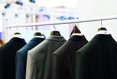Row of men's suits hanging on the rack.