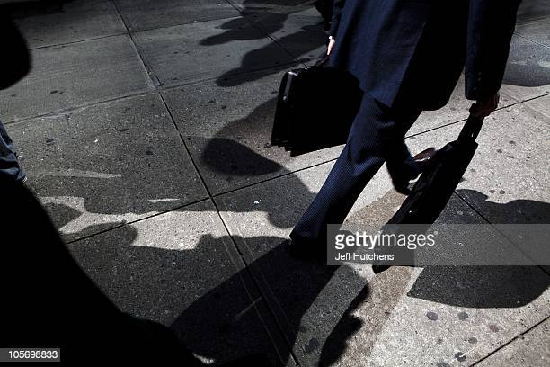 Suits walk by the more causally dressed on the streets of Midtown Manhattan home to many of the world's banks on April 9 2009 in New York City