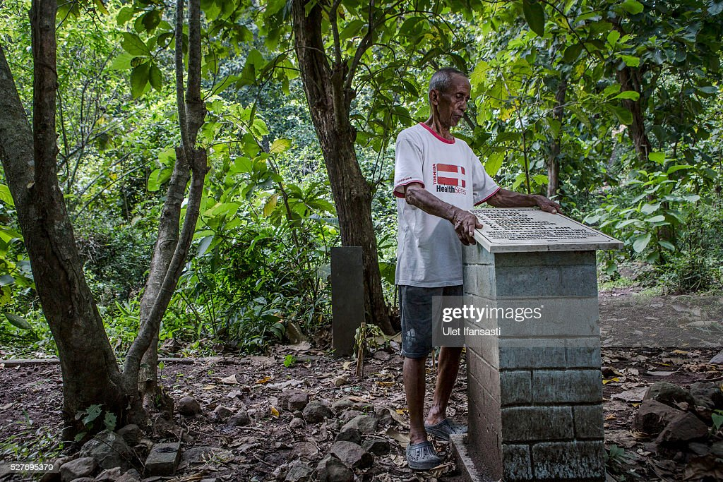 Sukar, 83 years old, a villager who witnessed Indonesia's anti-communist massacre, stands next to the tombstone which was installed by activists and families of victims on the site where it is believed victims were buried inside the teak forest in Plumbon village on May 03, 2016 in Semarang, Central Java, Indonesia. Sukar was ordered to bury victims of the massacre, who all had suspected ties to the Indonesian Communist Party (PKI). Survivors of Indonesia's anti-communist massacres called for investigations into the country's purges, in which possibly half a million to one million people died beginning October 1965, during the crackdown by the Indonesian government and military after an attempted coup by suspected communists.
