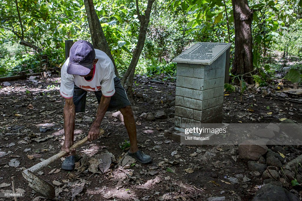 Sukar, 83 years old, a villager who witnessed Indonesia's anti-communist massacre, cleans near the tombstone which was installed by activists and families of victims on the site where it is believed victims were buried inside the teak forest in Plumbon village on May 03, 2016 in Semarang, Central Java, Indonesia. Sukar was ordered to bury victims of the massacre, who all had suspected ties to the Indonesian Communist Party (PKI). Survivors of Indonesia's anti-communist massacres called for investigations into the country's purges, in which possibly half a million to one million people died beginning October 1965, during the crackdown by the Indonesian government and military after an attempted coup by suspected communists.