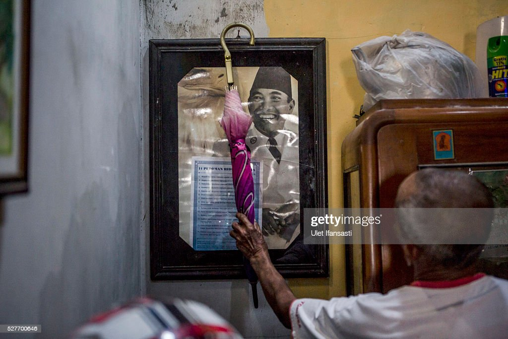 Sukar, 83 years old, a villager who witnessed Indonesia's anti-communist massacre, takes his umbrella off a poster of Indonesia's first President Sukarno hanging inside his house in Plumbon village on May 3, 2016 in Semarang, Central Java, Indonesia. Sukar was ordered to bury victims of the massacre, who all had suspected ties to the Indonesian Communist Party (PKI). Survivors of Indonesia's anti-communist massacres called for investigations into the country's purges, in which possibly half a million to one million people died beginning October 1965, during the crackdown by the Indonesian government and military after an attempted coup by suspected communists.