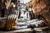 Sukhothai Historical Park, Thailand, traveller standing by ancient Buddha statue at Wat Si Chum temple.
