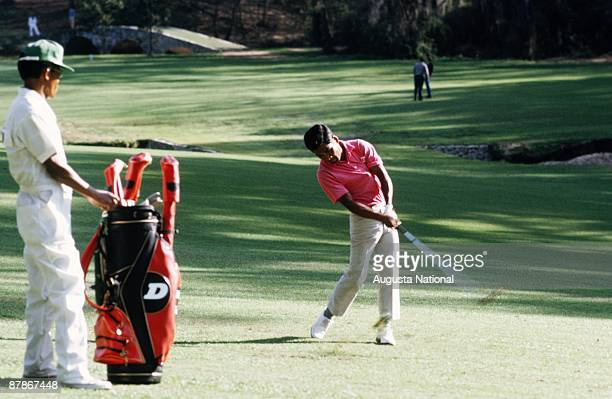 Sukree Onsham hits off the 13th fairway a part of Amen Corner while his caddie watches the 1971 Masters Tournament at Augusta National Golf Club on...