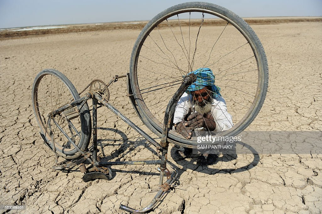 Sulemanbhai Sandhi, an Indian salt flat worker repairs a bicycle in the Santalpur region of Little Rann of Kutch, some 240 kms from Ahmedabad on March 7, 2013. Thousands of salt workers are deprived of basic amenities and the future of their children is uncertain as many schools lack adequate and experienced teaching staff. AFP PHOTO / Sam PANTHAKY