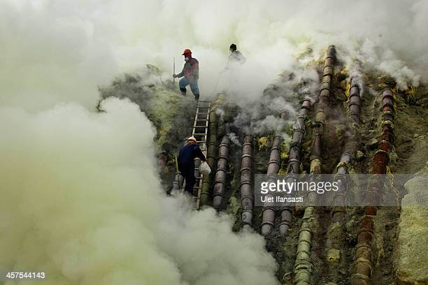 A sulfur miner carries a goats head in a white bag as he climbs to bury the head in the crater as part of an annual offering ceremony on the Ijen...