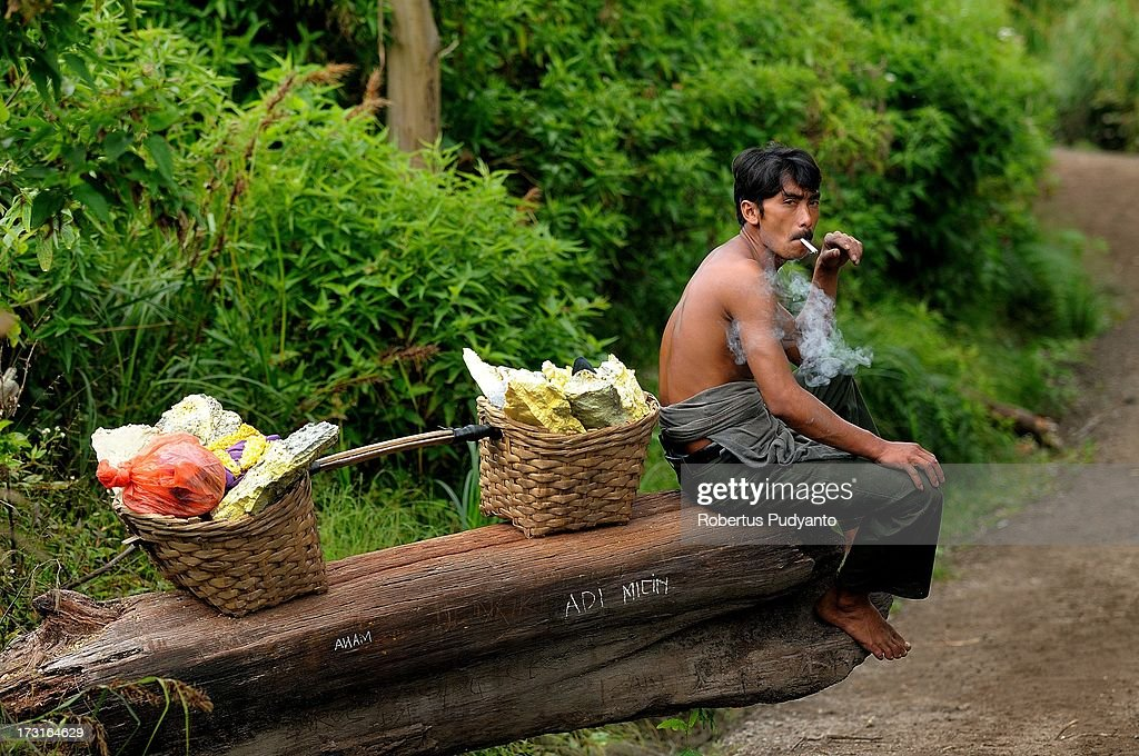 A sulfur miner carrying the two baskets of sulfur takes a break as he walks to the weighing station on July 9, 2013 in Arjuna, Java, Indonesia. Ijen Crater, which is known as Kawah Ijen, is located in the Ijen Volcano region, bordered by Banyuwangi and Bondowoso in East Java Province, Indonesia. Ijen Volcano is 2,600 meters tall (8,660 ft), topped with a large caldera and a 200 meter deep lake of sulfuric acid. The quietly active volcano emits gases through fumaroles inside the crater, and local miners have tapped those gases to earn a living. Stone and ceramic pipes cap the fumaroles, and inside the sulfur condenses into a molten red liquid, dripping back down and solidifying into pure sulfur. Miners hack chunks off with steel bars, braving extremely dangerous gases and liquids with minimal protection, then load up as much as they can carry for the more than 3 kilometers to the weighing station. Loads can weigh from 50 to 90 kg (100 - 200 lbs), and a single miner might make as many as two or three trips return in a day. At the end of a long day, miners take home approximately Rp. 50,000. The sulfur is then used for vulcanizing rubber, bleaching sugar and other industrial processes nearby. Sulfur widely used in fertilizer industry, cosmetics, skin disease drug, insecticides, paper, paints, plastics, petroleum processing, rubber and tire industry, sugar industry, batteries, chemicals industrial, explosives, weaving, film and photography, and also in metal or steel industry.