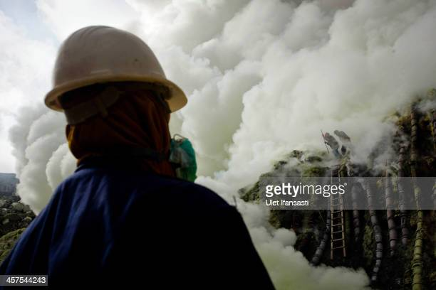 A sulfur miner looks at the crater as they prepare to bury the head in the crater as part of an annual offering ceremony on the Ijen volcano on...