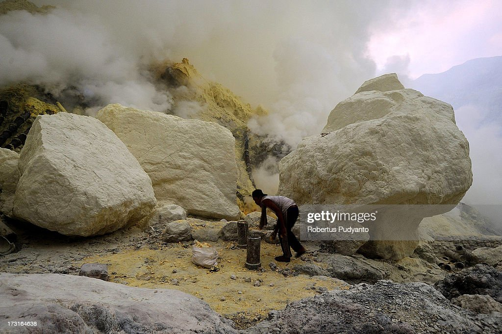 A sulfur miner tries to break sulfur chunks from a pipe flowing into Ijen Crater on July 9, 2013 in Arjuna, Java, Indonesia. Ijen Crater, which is known as Kawah Ijen, is located in the Ijen Volcano region, bordered by Banyuwangi and Bondowoso in East Java Province, Indonesia. Ijen Volcano is 2,600 meters tall (8,660 ft), topped with a large caldera and a 200 meter deep lake of sulfuric acid. The quietly active volcano emits gases through fumaroles inside the crater, and local miners have tapped those gases to earn a living. Stone and ceramic pipes cap the fumaroles, and inside the sulfur condenses into a molten red liquid, dripping back down and solidifying into pure sulfur. Miners hack chunks off with steel bars, braving extremely dangerous gases and liquids with minimal protection, then load up as much as they can carry for the more than 3 kilometers to the weighing station. Loads can weigh from 50 to 90 kg (100 - 200 lbs), and a single miner might make as many as two or three trips return in a day. At the end of a long day, miners take home approximately Rp. 50,000. The sulfur is then used for vulcanizing rubber, bleaching sugar and other industrial processes nearby. Sulfur widely used in fertilizer industry, cosmetics, skin disease drug, insecticides, paper, paints, plastics, petroleum processing, rubber and tire industry, sugar industry, batteries, chemicals industrial, explosives, weaving, film and photography, and also in metal or steel industry.