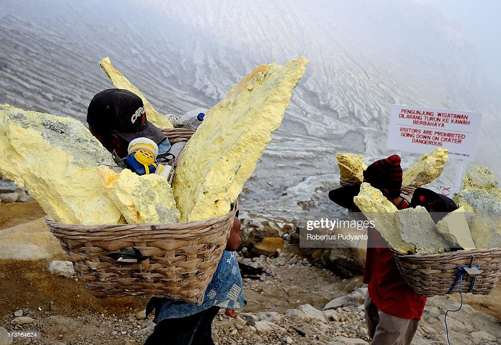 Sulfur miners carry baskets of heavy sulfur to a weighing station on July 9, 2013 in Arjuna, Java, Indonesia. Ijen Crater, which is known as Kawah Ijen, is located in the Ijen Volcano region, bordered by Banyuwangi and Bondowoso in East Java Province, Indonesia. Ijen Volcano is 2,600 meters tall (8,660 ft), topped with a large caldera and a 200 meter deep lake of sulfuric acid. The quietly active volcano emits gases through fumaroles inside the crater, and local miners have tapped those gases to earn a living. Stone and ceramic pipes cap the fumaroles, and inside the sulfur condenses into a molten red liquid, dripping back down and solidifying into pure sulfur. Miners hack chunks off with steel bars, braving extremely dangerous gases and liquids with minimal protection, then load up as much as they can carry for the more than 3 kilometers to the weighing station. Loads can weigh from 50 to 90 kg (100 - 200 lbs), and a single miner might make as many as two or three trips return in a day. At the end of a long day, miners take home approximately Rp. 50,000. The sulfur is then used for vulcanizing rubber, bleaching sugar and other industrial processes nearby. Sulfur widely used in fertilizer industry, cosmetics, skin disease drug, insecticides, paper, paints, plastics, petroleum processing, rubber and tire industry, sugar industry, batteries, chemicals industrial, explosives, weaving, film and photography, and also in metal or steel industry.