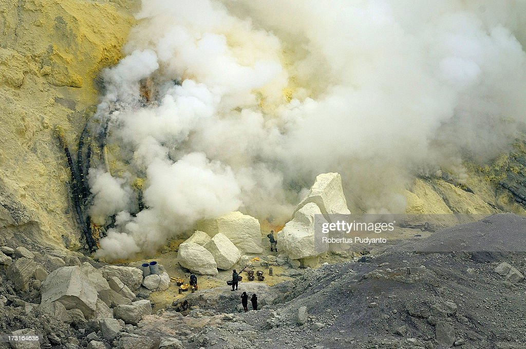 Sulfur miners try to break sulfur chunks from a pipe flowing into Ijen Crater on July 9, 2013 in Arjuna, Java, Indonesia. Ijen Crater, which is known as Kawah Ijen, is located in the Ijen Volcano region, bordered by Banyuwangi and Bondowoso in East Java Province, Indonesia. Ijen Volcano is 2,600 meters tall (8,660 ft), topped with a large caldera and a 200 meter deep lake of sulfuric acid. The quietly active volcano emits gases through fumaroles inside the crater, and local miners have tapped those gases to earn a living. Stone and ceramic pipes cap the fumaroles, and inside the sulfur condenses into a molten red liquid, dripping back down and solidifying into pure sulfur. Miners hack chunks off with steel bars, braving extremely dangerous gases and liquids with minimal protection, then load up as much as they can carry for the more than 3 kilometers to the weighing station. Loads can weigh from 50 to 90 kg (100 - 200 lbs), and a single miner might make as many as two or three trips return in a day. At the end of a long day, miners take home approximately Rp. 50,000. The sulfur is then used for vulcanizing rubber, bleaching sugar and other industrial processes nearby. Sulfur widely used in fertilizer industry, cosmetics, skin disease drug, insecticides, paper, paints, plastics, petroleum processing, rubber and tire industry, sugar industry, batteries, chemicals industrial, explosives, weaving, film and photography, and also in metal or steel industry.