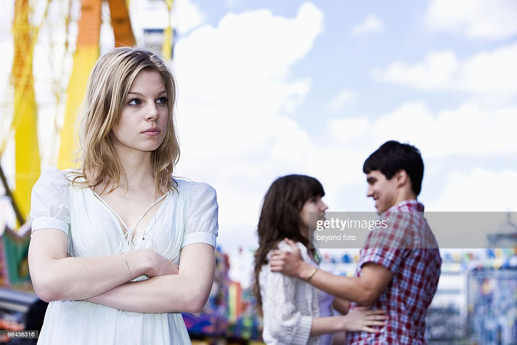 sulking teenage girl at fun fair with couple in background