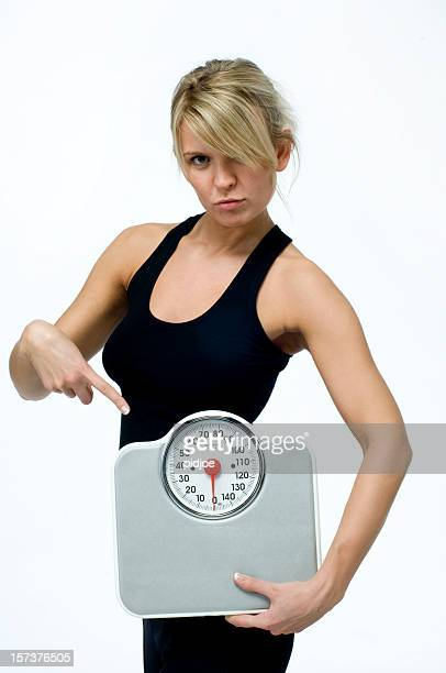 sulky woman pointing at weight scale