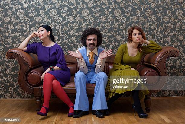 Sullen two women and a men sitting on sofa