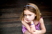 Sullen young girl sitting on porch with hands on chin