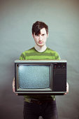 Sullen Young Man Holding Static Television