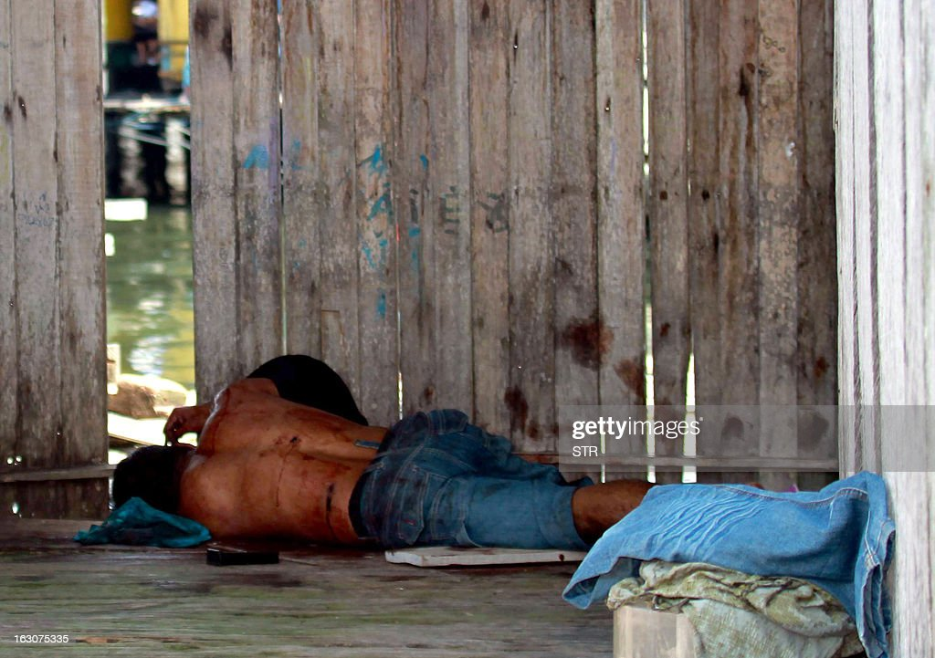 A Sulu gunmen who was shot dead, lies on the ground after a shoot-out with soldiers in Simunul village on March 4, 2013. Malaysia vowed to beef up security in the eastern state where at least 26 people have been reported killed after a bizarre invasion by Philippine followers of a self-styled sultan. AFP PHOTO MALAYSIA OUT
