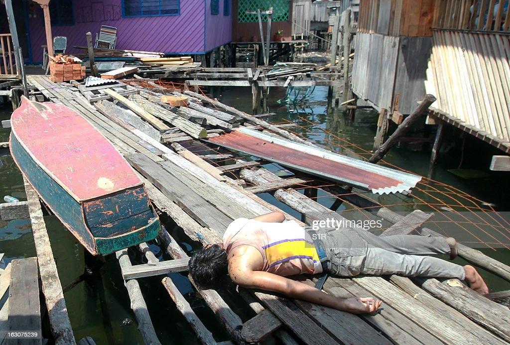 A Sulu gunmen who was shot dead, lies on the wooden planks after a shoot-out with soldiers in Simunul village on March 4, 2013. Malaysia vowed to beef up security in the eastern state where at least 26 people have been reported killed after a bizarre invasion by Philippine followers of a self-styled sultan. AFP PHOTO OUT
