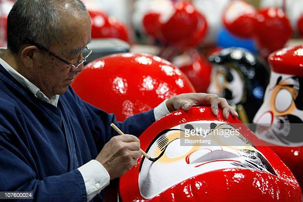 Sumikazu Nakata a daruma doll craftsman and president of the Gunma Daruma Manufacturers Association paints on a face of a 'Daruma' doll at his...