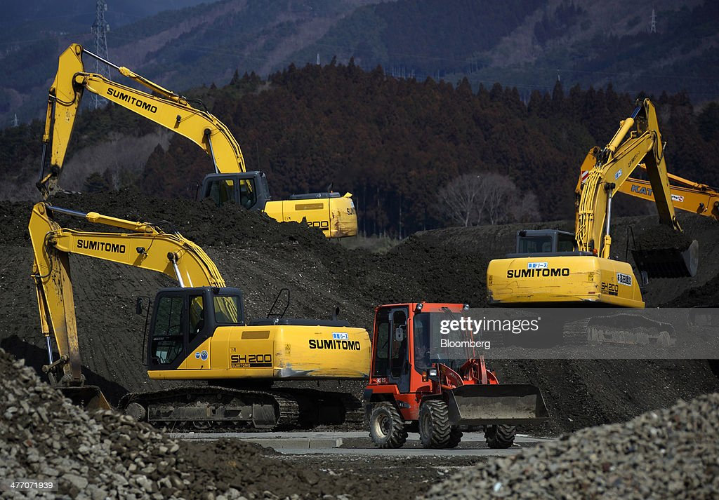 Sumitomo Construction Machinery Co. excavators operate on a construction site in Rikuzentakata, Iwate Prefecture, Japan, on Thursday, March 6, 2014. Reconstruction of Tohoku, the northern Japan region devastated by the 2011 tsunami, continues as the third anniversary of the disaster approaches. Photographer: Tomohiro Ohsumi/Bloomberg via Getty Images