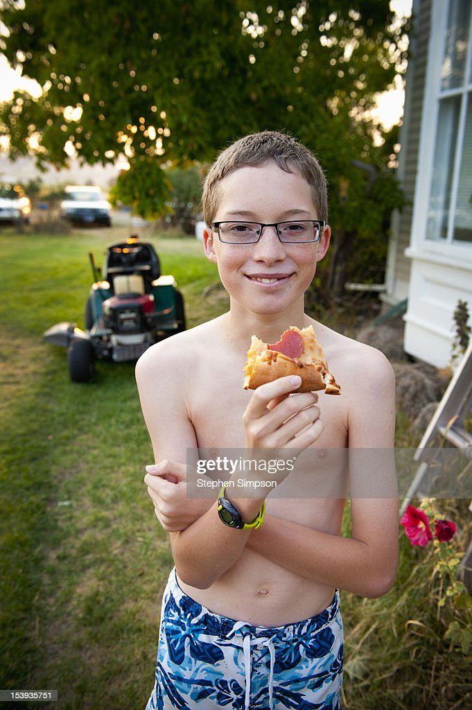 Summer afternoon, boy eating pizza on front lawn : Stock Photo