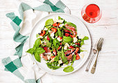 Summer arugula, prosciutto and strawberry salad with glass of rose wine over white painted wooden background, top view, horizontal composition