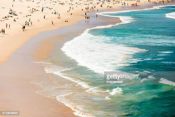 Verão na praia e mar com multidão de banhistas