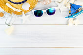 Summer Beach accessories (White sunglasses,starfish,straw hat,glass bottle,shell) on white plaster wood table top view,Summer vacation concept,Leave space for adding text.