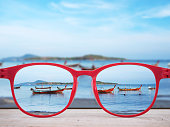 Summer beach at Phuket Thailand focused in red glasses lenses